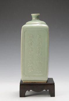Chinese Square Celadon Vase, 18th C or Earlier. Two sides are carved with calligraphy and the other two with floral scrollwork, one of those sides having characters as well.