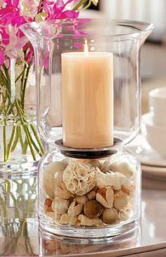 "Beautiful glass hurricane that makes a stunning centerpiece or accent piece. Fill the bottom chamber with stone, potpourri, seashells or sand from vacation. Holds a 3"" x 6"" Pillar Candle. 6 1/8""d (base) x 11 3/4""h; 8"" opening at top  $34.00"