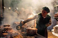 Winner of the Food for Celebration category: Mark Benham's Food Stall, Medieval Festival shows a chef dressed in medieval costume fanning the coals below meats cooking on a grill as smoke wafts through the air