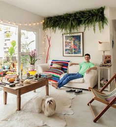 Objetos improváveis - como galhos de árvores, mesas e cadeiras salvas de caçambas e lâmpadas de festas de São João - compõem a decoração inusitada da sala de estar do diretor de arte de cinema Thiago Bastos