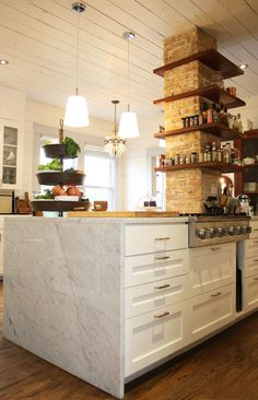 this is a totally new kitchen idea I hadn't seen before.  exposed brick column with built in shelving for use and display