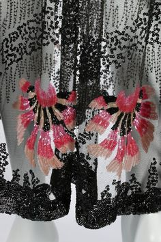 A beaded tulle cocktail dress, circa 1915-20. adorned with zig-zagged steel beads, vermicular black sequins and large pink carnation palmettes, with beaded rope belt which slots through and ties over one hip, pointed side panels edged in beaded tassels