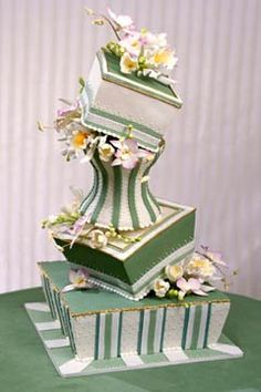 Fabulous, chic, creative, whimsical and elegant wedding bridal  cake with unbalanced tilting tiers in an asymmetrical design featuring stripes and flowers in a palette of green, white, yellow and pink.