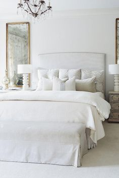 Chic white bedroom with upholstered headboard, matching geometric finial table lamps, matching tall antique French gold mirrors, vintage nightstands, slipcovered bench at the foot of the bed, and white carpet underfoot.