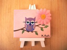 Tiny Sleepy Owl. A lovely hand painted owl made with care and detail on a 100% cotton canvas! This charming artwork is an original and unique piece (NOT A PRINT), created with fine quality acrylic paints, mostly in pink and purple and then embellished with a pink flower. A lovely example of owl art, perfect for girls' bedrooms. This miniature owl painting with easel makes a great present and a last minute gift idea for little girls or teenagers.