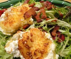 Warm goat cheese salad with frisée lettuce, bacon lardons, and rounds of lightly breaded goat cheese, browned so they are warm and melty on the inside and crispy on the outside.