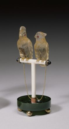 Perched on a T-shaped ivory stand is a pair of topaz cockatoos with ruby eyes and gold feet. They are connected by gold chains to a pink enamel and gold mount set in a nephrite base supported by four gold ball feet. Carl Fabergé was particularly fond of birds and kept a pet cockatoo.