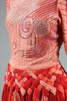 Valentino couture evening gown, circa 1985-8, un-labelled, of deep peach crêpe, the bodice covered in swirls of bugle beads and rhinestones, the skirt formed from pleated interwoven godets of chiffon in shades of deep wine to peach.