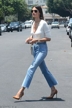 Stunner:The Victoria's Secret Angel paired the retro trousers with a plunging white crop top and chic suede camel pumps