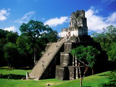 Tourists climb Pyramid II to reach the Temple of the Masks in the Maya city of Tikal. Guatemala,