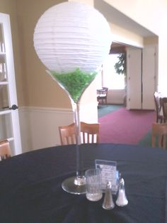 Cute centerpiece idea for golf event. Giant martini glass filled with fake grass and topped with white small chinese lantern. Very cute!