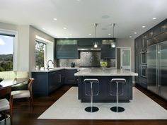 This kitchen puts a new spin on contemporary style, with a textured metal backsplash and sleek, teal cabinets. Stools at the large island and a dining nook by the window invite family and friends to gather for casual meals.