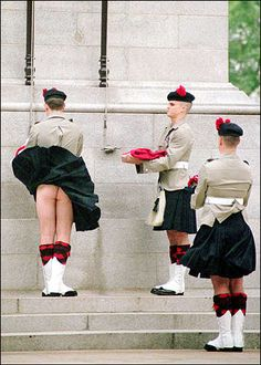 April 24, 1997, Hong Kong:  Lance Corporal Lee Wotherspoon of the Black Watch (RHR) lowers the Union Jack as the wind raises his kilt at the daily lowering of the flag at Hong Kong's Cenotaph prior to the former British Colony being handed over to China on July 1, 1997.  Apparently, he received romantic letters from several women and a few men around the world admiring his attributes -- reportedly he was rebuked by his commander only because his sock-tops were not level!
