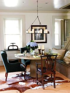 A Candle Style Iron Chandelier And Cowhide Rug Are Little Bit Country But The Custom Made Contemporary Table Classic Wing Chair Give This Dining Room