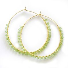 Handmade hoop earrings are wire wrapped with glittering, faceted peridot gemstones. Available in 14 karat gold-filled or .930 Argentium silver in two stock sizes: Small - 1.5 inch (3.18 cm) diameter L