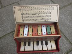 """Antique European Toy Piano of wood and cardboard with metal """"xylophone"""" or Glockenspiel sound plates."""