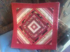 Kussenhoes gemaakt van restjes rode en witte stoffen.