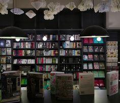 Lutyens & Rubenstein, London bookshop in Notting Hill, book sculptures hanging from ceiling, black book shelves, modern globe pendants