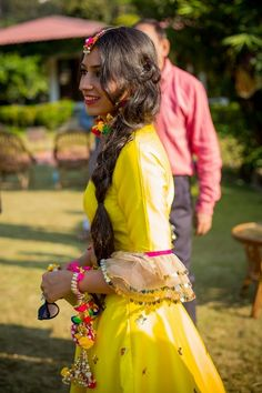 Mehendi Outfits - Yellow Satin Lehenga with Frills | WedMeGood | Yellow Blouse with Frilly Sleeves, Colorful Pom-poms as Jewelry #wedmegood #indianbride #mehendioutfit #mehandioutfit #mehendi #yellow #pom-poms #frills #indianwedding