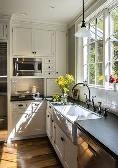 Amazing wood floors with white cabs and soapstone countertops, farmhouse sink