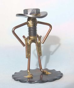 WELDED NUT and BOLT COWBOY GUNSLINGER  There is just 1 of these Cowboy Gunslingers. They were made about 25 years ago by a friend and, sadly, I can get no more. They are very cute and, like the other little Cowboy Sculptures, make a great stocking stuffer.  The Gunslinger stands 3 inches tall and is on a base that is 2 inches in diameter. Weight is just a little more than 2 ozs and when boxed for shipping the weight will be 8 ozs. Price for this little Cowboy is $10.00 and shipping is $4.00…