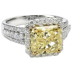 Natural Fancy Yellow Radiant Cut Diamond GIA Certified Ring - A mesmerizing Natural Fancy Yellow Radiant Cut Diamond is featured in this beautiful handmade 18kt White and Yellow Gold Ring. The center stone is 4.09ct and is surrounded by Brilliant cut Diamonds, GIA cert. On sale 98k$