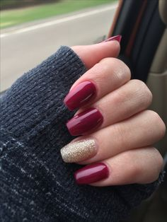 Burgundy nails with gold design.