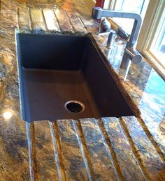 Copper or Silgranite sink undermounted in thick granite coutertops with water drain runnels.