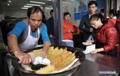 """A cook makes """"doupi"""", a snack made of bean curd, at a snack bar in Changsha, capital of Hunan province, February 3, 2014. To many Chinese people, traditional snacks are part of the Spring Festival and the taste of hometown"""
