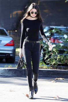 Kendall Jenner does a cool take on a monochrome look in a black top, skinny jeans, chain belt, choker, aviator sunglasses, and cowboy boots