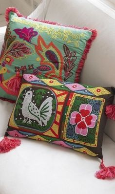 Colorful Mexican cushions covered in embroidered patterns of birds, flowers and leaves.