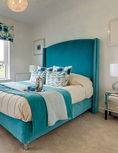 Colorful master bedroom decor in bright blue - white tones, velvet bed, delicate bedding details plus mirrored table bed with gorgeous lamp and chandelier, in coastal Scotland.
