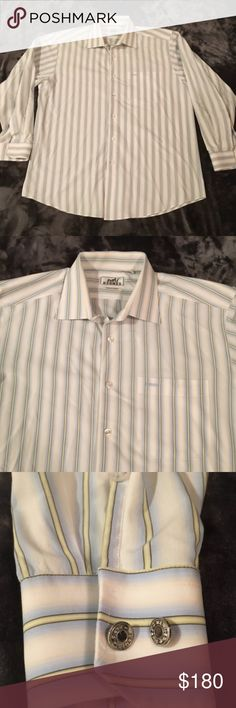 "Vintage HERMES Striped L/S Button Down -Size 17/42 Authentic vintage men's HERMES Paris long sleeve button down shirt in a size 17/42.  White shirt with blue and yellow stripes. Has two metal buttons on each cuff with the ""Hermes Paris"" inscription. The logo on the front of this shirt actually says Hermes, compared to the newer shirts that have the design. The shirt itself is in excellent condition, with no stains, holes or rips. The only sign of wear is the metal cuff buttons are a bit…"