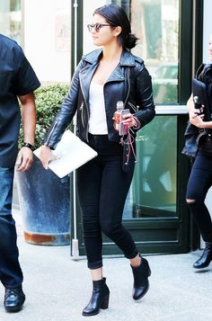 Selena Gomez wears a moto leather jacket with cuffed black jeans, ankle booties and a white top.