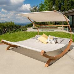 Look what I found on Wayfair! Unwind poolside or on the patio on this understated double chaise lounge, featuring a curved wood base, sling seat, canopy top, and 2 complementing throw pillows.