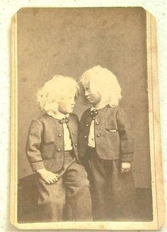 Genuinely creepy. POSSIBLE post mortem photo of the twin on the right.  Stands were sometimes used to make the deceased seem alive.  The R. Twins skin is discolored, the eyes are lifeless, arm hangs at his side and there's an unnatural leaning to his stance, whereas his brother has turned his head and is glancing up at him with trepidation. Live Siblings and surviving twins were often posed with their deceased siblings for post-mortem photos.