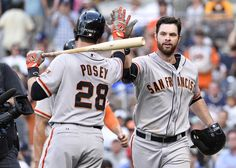 Brandon Belt #9 of the San Francisco Giants, right, is congratulated by Buster Posey #28 after he hit a two-run home run during the tenth inning of a baseball game against the San Diego Padres at Petco Park July 5, 2014 in San Diego, California. (July 4, 2014 - Source: Denis Poroy/Getty Images North America)