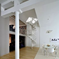 """a standard-issue spiral staircase painted white becomes sculpture in a double-height space designed by NYC-based architect David Hotson"""