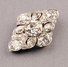 Art Deco Platinum and Diamond Clip, of navette form, prong-set with an old European-cut diamond weighing approx. 2.25 cts., and further set with old European, pear, and old single-cut diamonds, approx. total wt. 6.50 cts., millegrain accents, finely pierced clip back, lg. 1 1/4 in.