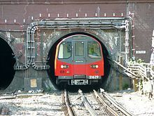 A northern line deep-tube train leaves a tunnel mouth just north of Hendon Central Station