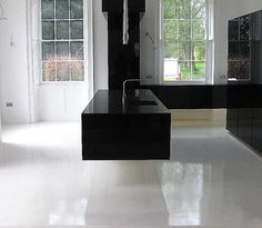 Ultra modern gloss black floating cantilevered kitchen  with pure white seamless resin floor