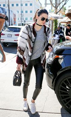Kendall Jenner wears a choker, gray t-shirt, patchwork fur coat, leather leggings, white sneakers, aviator sunglasses, and a mini satchel