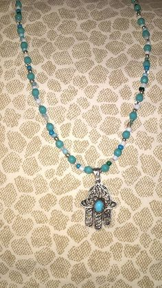 A hamsa I acquired in Cairo, Egypt.   Added to a beaded necklace I made just for the hamsa.