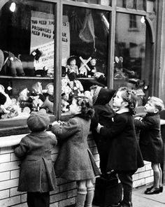 Children at a toy store window. My dad once told my brother he could have anything he wanted from a window like this. My brother chose a Dinky motor bike. Austerity was bred into us.
