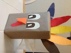 Thanksgiving turkey tissue box craft  All Supplies from the dollar store. Cover tissue box with brown postal wrap, glue on construction paper feathers.