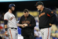 San Francisco Giants' Brandon Belt, left, reacts after being hit by a pitch on his left hand as a trainer and manager Bruce Bochy, right, at...