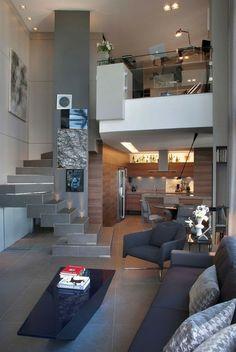 maison moderne de luxe dans une pièce plafond haut, canapé et fauteuils en bleu canard, escalier angulaire sans garde corps,