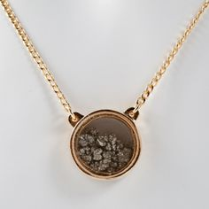 Pyrite becomes the star of this gold pendant, filling the glass locket with its shimmering, ghostly hue.