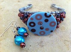 A button and a wire-wrapped cuff bracelet
