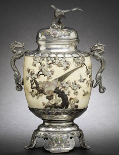 A Shibayama-style inlaid silver and ivory vase and cover by Nagaoki and Tsunemasa, Meiji Period The ivory body richly inlaid in various materials with two quail, a pheasant and small birds among chrysanthemums, peonies and a flowering cherry tree, the shoulders and foot of silver inlaid with formal scrolling foliage in coloured enamels and the shoulders mounted with dragon handles, the cover bears similar enamel designs and is surmounted by a finial in the form of an alighting hawk